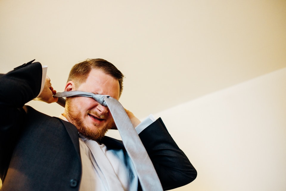 funny shot of groomsman putting on tie