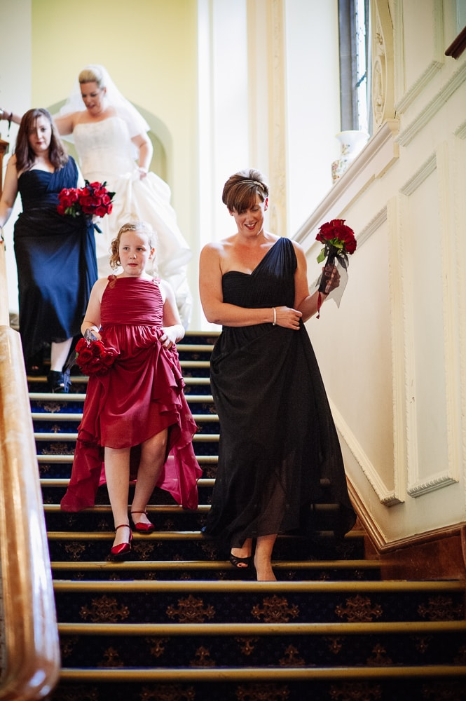 flower girl and bridesmaid walking downstairs in black and red dresses