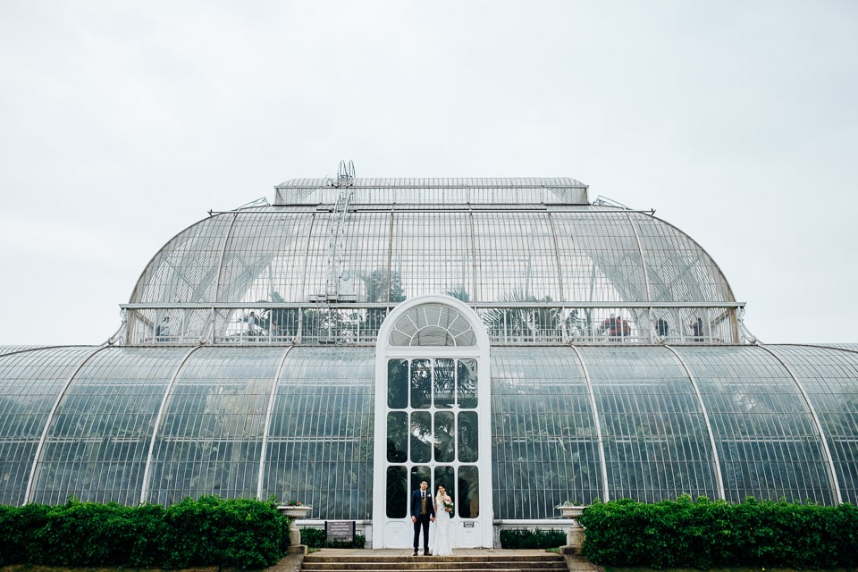 bride and groom outside palm house in kew gardens