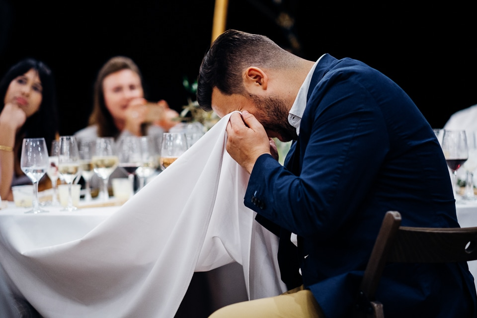 man crying into table cloth